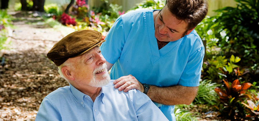 elderly man and younger carer