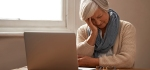 An elderly woman sitting in front of her laptop looking stressed and worried