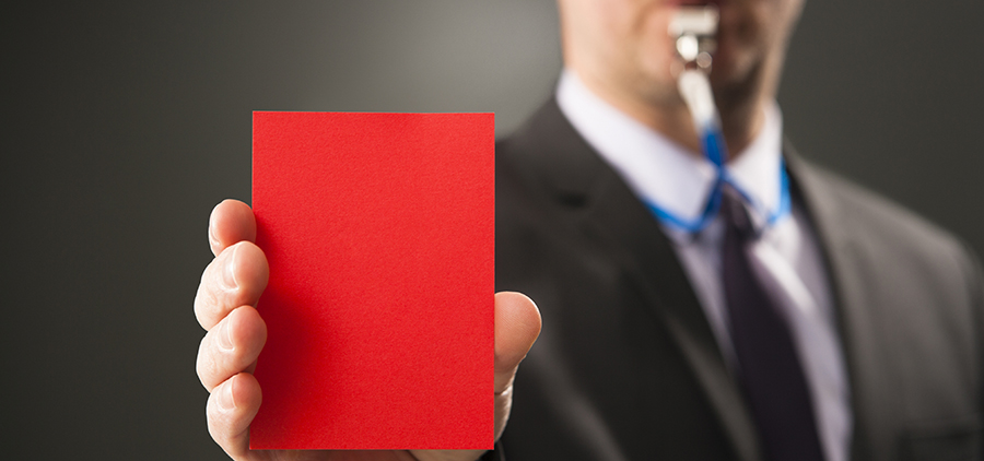 Businesman blows whistle and shows red card